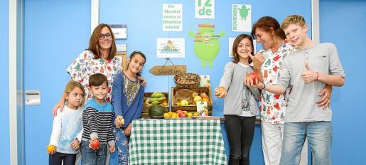 Niños enseñan diferentes frutas durante la celebración del Día Mundial contra la Obesidad Infantil.