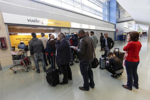 Imagen de archivo de pasajeros de un vuelo de Vueling esperando frente a la oficina del aeropuerto de Ibiza para reclamar.