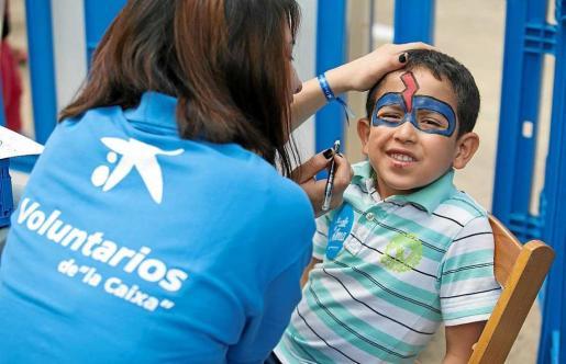 Una integrante de Voluntarios de 'la Caixa' pinta la cara de un niño.