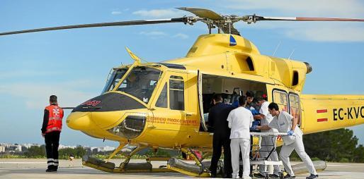 Los trabajadores del Hospital de Formentera y los pilotos realizando el traslado de un paciente al aparato.