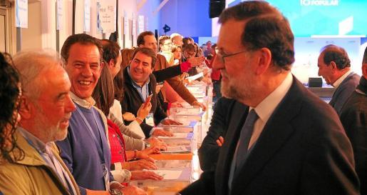 El presidente del Gobierno y líder del PP, Mariano Rajoy, saludando a los compromisarios.