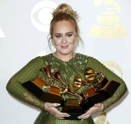 Adele, sujetando sus premios.