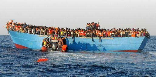 Una barco desbordado de personas es auxiliado en el mar por una lancha de la ONG Proactiva Open Arms. g Foto: G. Moutafis