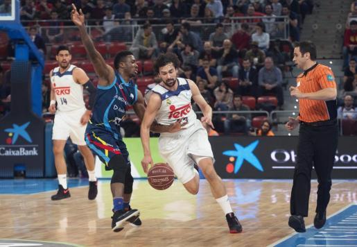 El base del Real Madrid, Sergio Llull avanza ante la presión del alero norteamericano del Basquet Andorra David Walker.