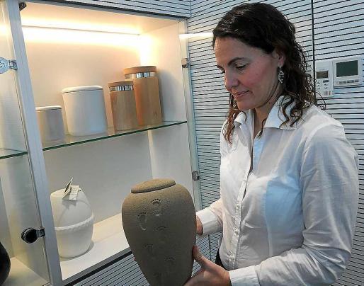 La gerente del crematorio muestra una urna para cenizas elaborada con arena.