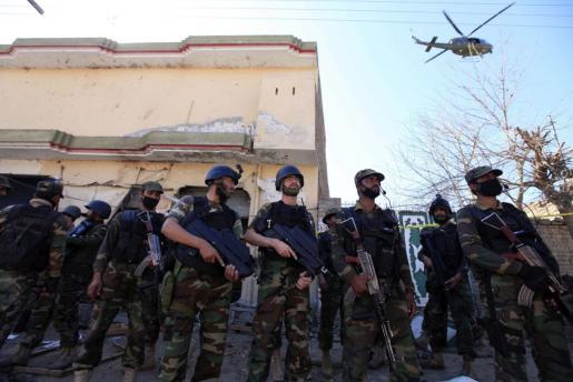 Oficiales de seguridad aseguran la zona en la que han hecho explosión tres bombas durante un ataque suicida en Peshawar (Pakistán).
