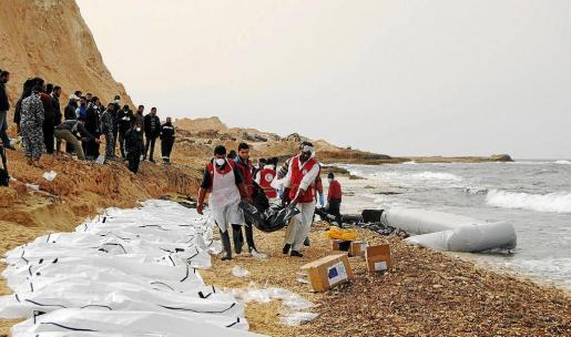 Personal de la Media Luna Roja libia coloca en una hilera los cadáveres rescatados frente a las playas de la ciudad de Zawiya.