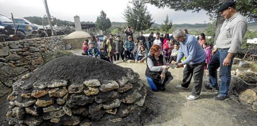 Miquel D'en Trull encendió ayer por la mañana la 'sitja' en compañía de Toni Boned y los niños del colegio público de Santa Agnès de Corona.