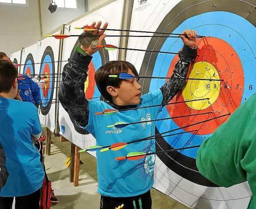 Uno de los participantes retira las flechas clavadas en la diana.