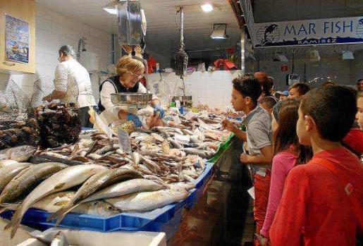Sobre estas líneas, Conchi le explica a los niños los secretos de su puesto de pescado. Foto: C. C.
