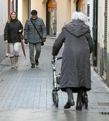 Una mujer mayor paseando sola por la calle.