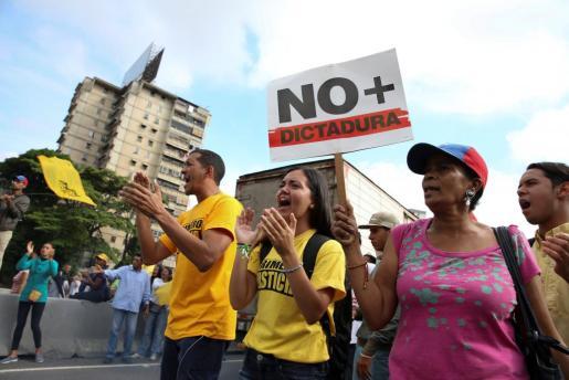 Un grupo de opositores venezolanos piden el fin de la dictadura.