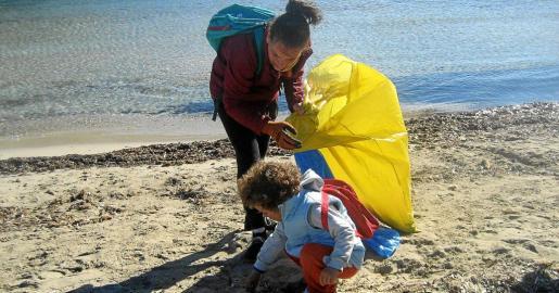 Una voluntaria camina por la orilla retirando desperdicios de la playa mientras educa y conciencia a su hijo en la conservación del entorno natural.