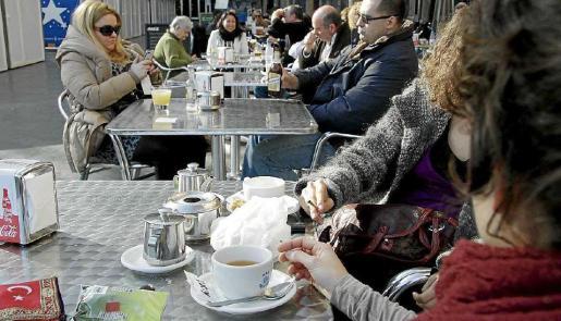 Gente fumando en la terraza de un bar al aire libre, así si que se cumple la legislación.