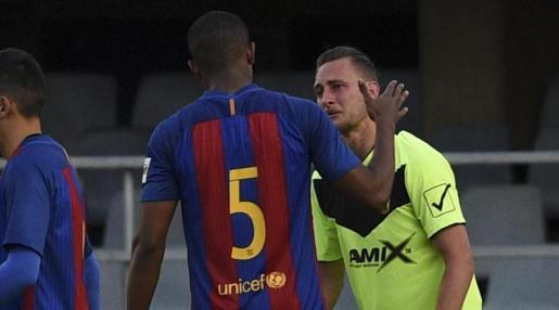 Un jugador del Barça trata de animar a otro del club alicantino, llorando en el terreno de juego tras la abultada derrota.