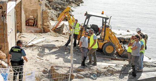 Un agente de la Guardia Civil se dirige al grupo de operarios que habían empezado a vaciar una de las cinco casetas que serán demolidas.