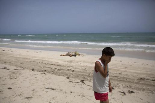 Un niño camina junto a los cuerpos sin vida de inmigrantes que han aparecido en una playa en Zuwarah al oeste de Trípoli en Libia.