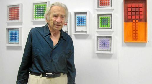 El artista uruguayo, afincado en Ibiza desde hace 40 años, posa junto a algunas de sus obras pictóricas de pequeño formato en la libreria Espressarte.