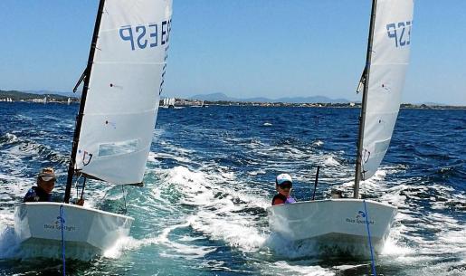 Quidel Villalba, en el optimist de la derecha, mientras navega a remolque junto a un compañero del CNSA.