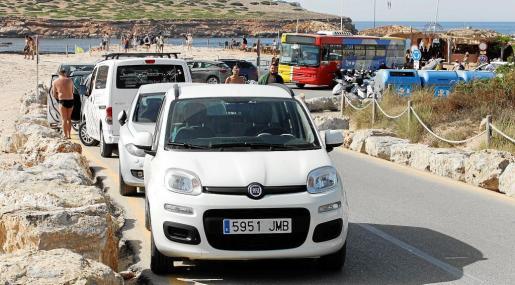 Decenas de vehículos aparcados junto a la línea amarilla y ocupando un carril, a pesar de la señal de prohibido aparcar y aviso a la grúa.