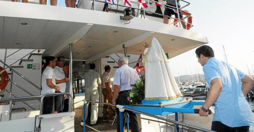 Momento en que la imagen de la virgen del Carmen accede a la embarcación para navegar por la Bahía de Sant Antoni.