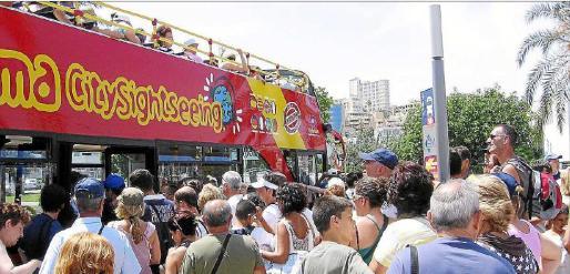 Turistas aguardando en cola para subir al autobús turístico y recorrer Palma.
