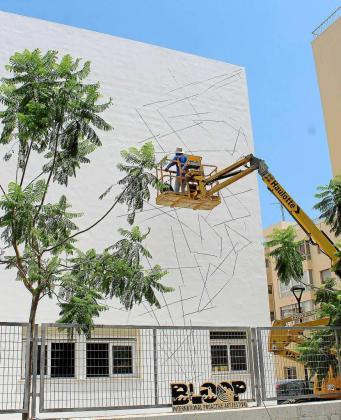 El artista griego Ino, comenzando a realizar su obra en el colegio Sa Graduada de Ibiza.