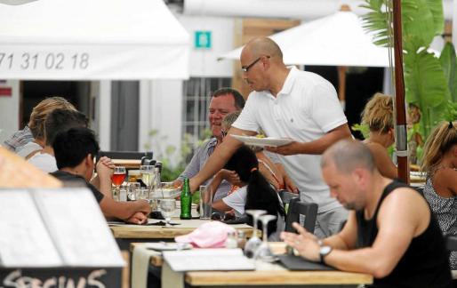 El paro se reduce en todos los sectores, especialmente en el de servicios, con 443 parados menos que hace un año. En la imagen, un trabajador atiende la mesa de una terraza llena de gente en el centro de Vila.