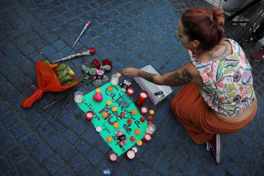 """A woman places a candle on a placard, reading in Spanish and Catalan """"Catalonia, place of peace"""", in the area where a van crashed into pedestrians at Las Ramblas street in Barcelona, Spain August 18, 2017. REUTERS/Sergio Perez SPAIN-BARCELONA/"""