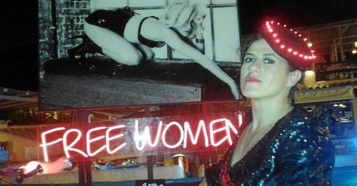 Diana Gómez posando frente a la imagen y el cartel de neón que lleva el nombre de su estrenada exposición 'Free Women'.