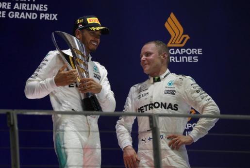 El piloto Lewis Hamilton celebra su primer puesto en el podio del Gran Premio de Singapur, junto con Valtetri Bottas.