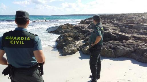 Imagen de archivo de dos agentes de la Guardia Civil inspeccionando la zona de la platja de Llevant donde un vecino localizó en octubre de 2016 una embarcación abandonada.