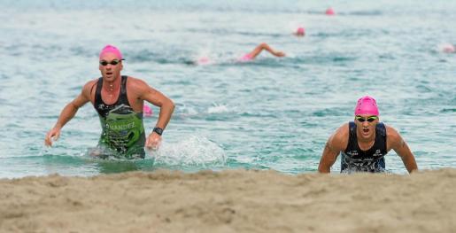 Instante en el que dos participantes se disponen a abandonar el agua para comenzar el último segmento a pie.