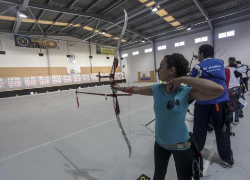 Un grupo de arqueros se dispone a lanzar sus flechas hacia las dianas en un torneo de tiro en sala.