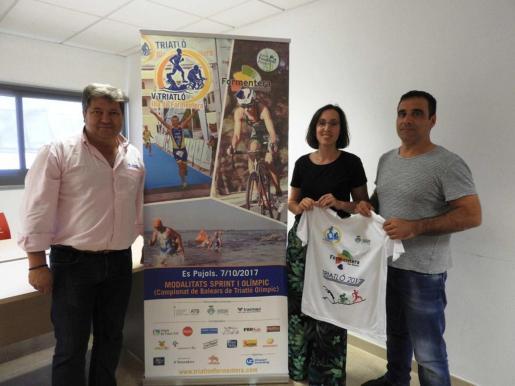 Jordi Vidal, Nuria de la Torre y Manuel Hernández, posan junto al cartel promocional del Triatló Illa de Formentera.