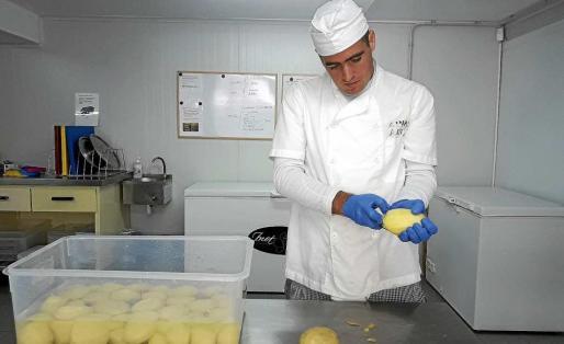Un trabajador del centro colaborando en la cocina para preparar los 80 menús diarios.