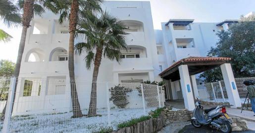 Imagen de la entrada del complejo residencial donde se aprecia el ajardinamiento, el vallado perimetral y el pintado de la fachada de color blanco.
