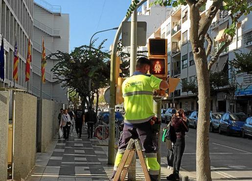 Un operario del Consistorio, ayer, en avenida Espanya instalando el semáforo paritario.