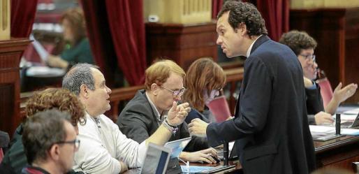 El conseller de Territori, Marc Pons, y el diputado de Podemos Aitor Morrás en el pleno del Parlament.
