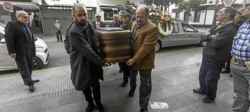 El concejal de Cultura i Patrimoni del Ayuntamiento de Ibiza Pep Tur ayuda a introducir el féretro de Toni Pomar en presencia de su hijo, el fotógrafo Toni Pomar Bofill.