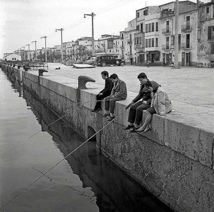 En la imagen, dos amigos y una pareja de enamorados pescando en el puerto de Ibiza, junto a la Marina.
