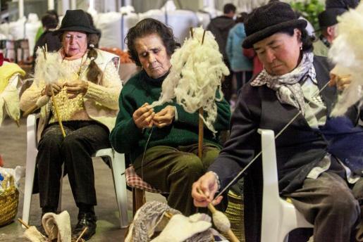 Tres mujeres hilando lana como se hacía antiguamente.