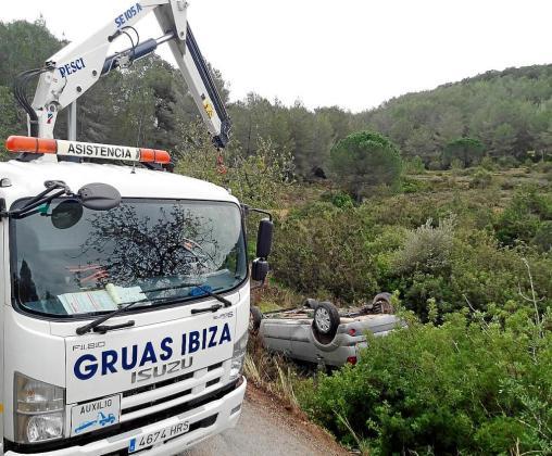Uno de los coches implicados en el siniestro acabó volcado fuera de la carretera y fue recuperado por técnicos de auxilio en carretera de Grúas Ibiza.