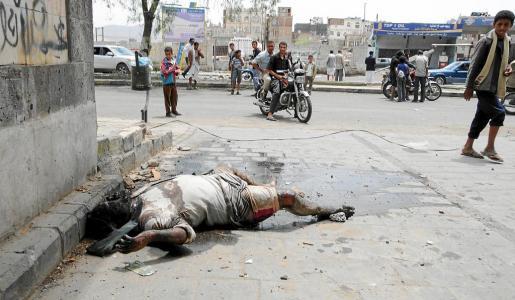 Varias personas observan el cuerpo sin vida de un miliciano tribal del líder opositor Sadeq al Ahmar.