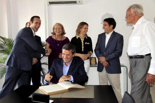 Las autoridades con Klaus Fraf y Pere Rotger firmando en el libro de honor.
