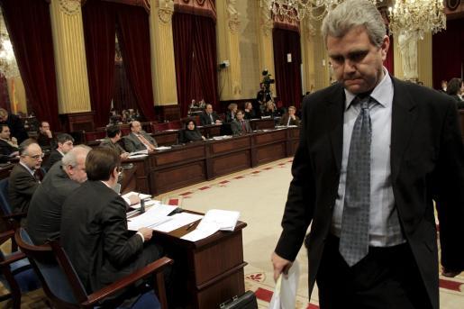 Un cabizbajo Josep Melià abandona la tribuna de oradores tras su intervención. A la izquierda, Antich y Moragues.