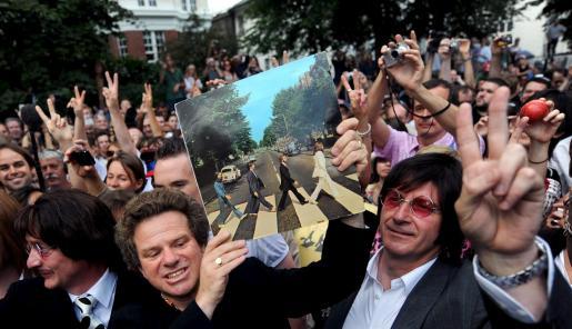 """EFE - REINO UNIDO-BEATLES - ACE - MUSIC - ARA2 LONDRES (REINO UNIDO) 08.08.09.- El guía Richard Porter (c) sostiene una copia del disco """"Abbey Road"""" en esta calle de Londres, Reino Unido, hoy sábado 08 de agosto. Un gran número de seguidores del grupo de Liverpool se ha acercado a este lugar para cruzar por su famoso paso de cebra con motivo del cuarenta aniversario del lanzamiento este álbum. EFE/Andy Rain REINO UNIDO-BEATLES - London - United Kingdom - ANDY RAIN - tmc"""