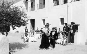 Una pareja de 'balladors', vestidos ambos con trajes de 'gonella negra', realizan los movimientos finales de uno de los bailes tradicionales de las Pitiüses. Foto: XICU BUFÍ.