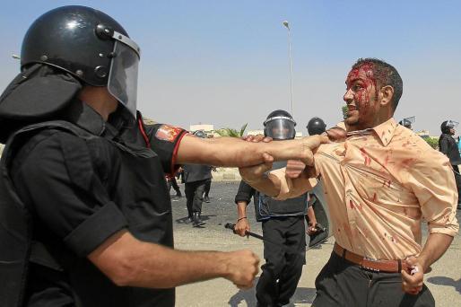 Un agente de la policía antidisturbios sujeta a un manifestante anti-Mubarak herido por una pedrada.