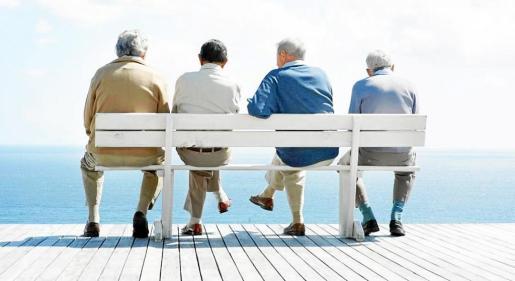 Un grupo de jubilados sentados en un banco frente al mar, disfrutando del buen tiempo y de las horas de descanso, después de haber tenido que trabajar durante muchos años.